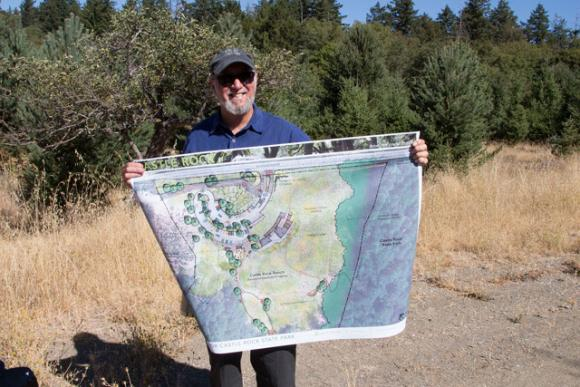 Reed Holderman of Sempervirens Fund displays an artist's rendering of the new Castle Rock entryway. Mike Kahn photo.