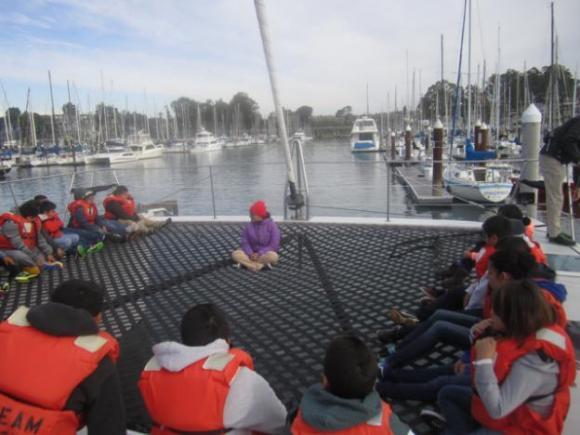 Celia Lara of O'Neill Sea Odyssey gives fifth graders from Watsonville's Ann Soldo Elementary School  an orientation on the O'Neill Catamaran's mesh deck.
